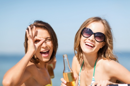 nonalcoholic beer: summer holidays and vacation - girls in bikinis with drinks on the beach chairs