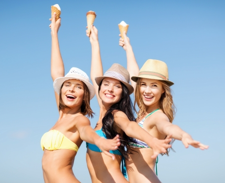 women having fun: summer holidays and vacation - girls in bikinis eating ice cream on the beach Stock Photo