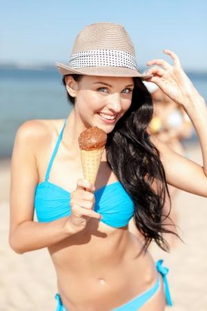 summer holidays and vacation - girl in bikini eating ice cream on the beach photo