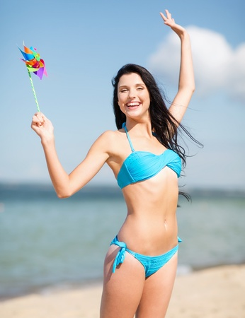 summer holidays, vacation and ecology concept - girl with windmill toy on the beach photo
