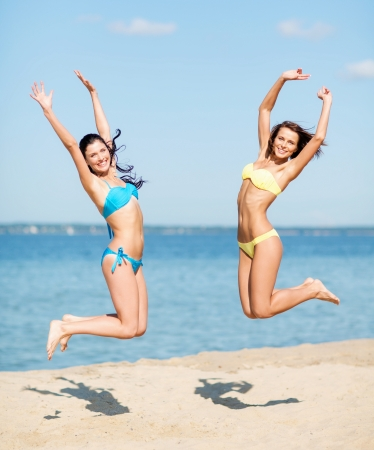 sexy women body: summer holidays and vacation concept - beautiful girls in bikini jumping on the beach