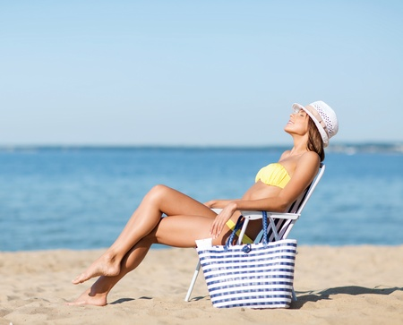 chaise longue: summer holidays and vacation - girl in bikini sunbathing on the beach chair