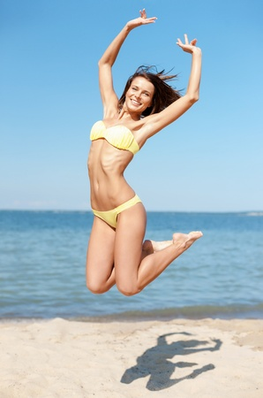 bikini sexy: summer holidays and vacation concept - beautiful woman in bikini jumping on the beach