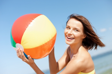 playing in the sea: summer holidays, vacation and beach activities concept - girl in bikini playing ball on the beach