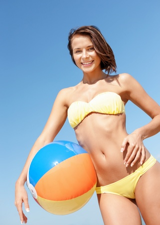 weekend activities: summer holidays, vacation and beach activities concept - girl in bikini with ball on the beach