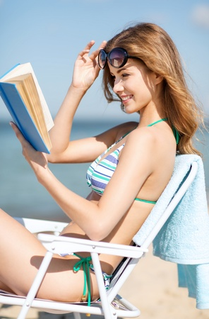 summer holidays and vacation - girl reading book on the beach chair photo