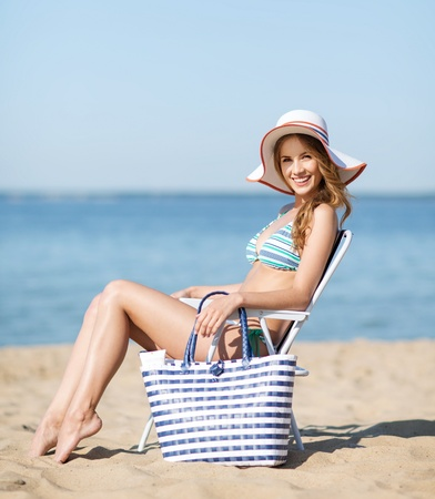 summer holidays and vacation - girl in bikini sunbathing on the beach chair photo