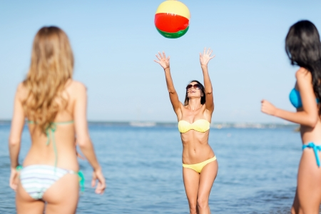 summer holidays, vacation and beach activities concept - girls in bikinies playing ball on the beach photo