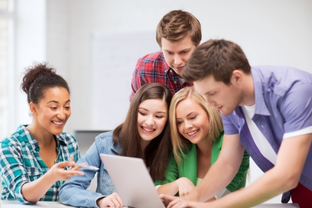 education and internet concept - group of international students looking at laptop at school photo