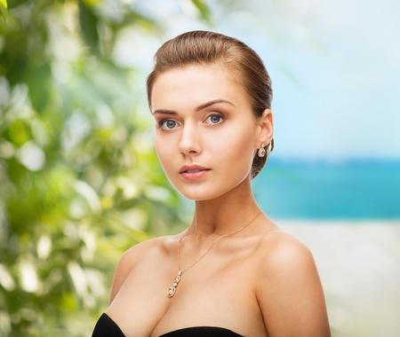 beauty and jewelry concept - woman wearing shiny diamond earrings photo