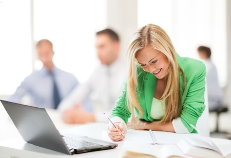making notes: business concept - attractive businesswoman taking notes in office
