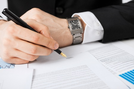 business  deal: close up picture of man hand signing contract Stock Photo