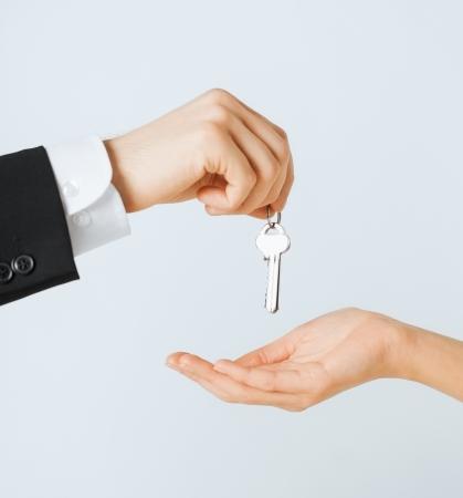 여자에게 집 열쇠를 건네주는 남자 손의 그림
