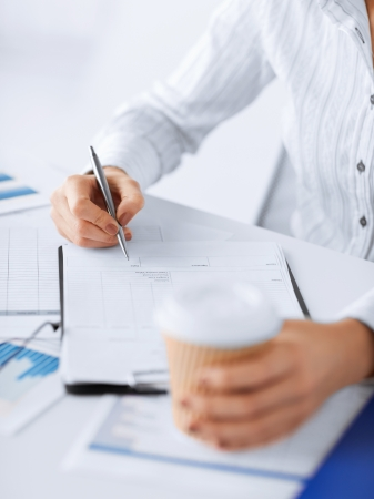 picture of woman hand filling in blank paper and drinking coffee