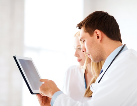radiology: healthcare and medical - two doctors looking at x-ray on tablet pc Stock Photo