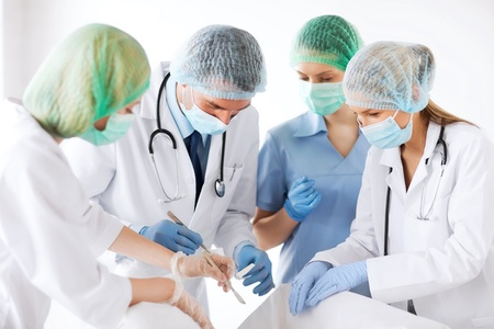 healthcare and medical - young group of doctors doing operation Stock Photo