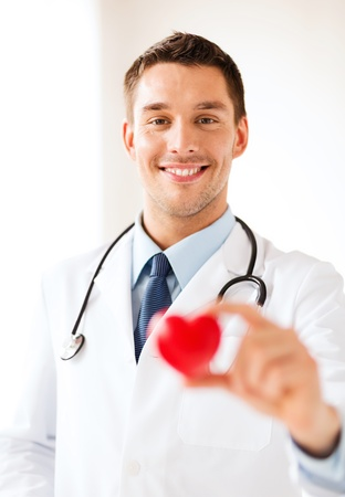heart doctor: healthcare and medical concept - male doctor with  heart