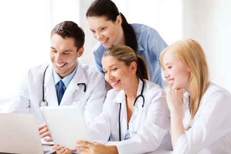 new medicine: healthcare, medical and technology concept - group of doctors looking at tablet pc