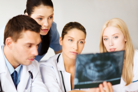 healthcare, medical and radiology concept - group of doctors looking at x-ray photo