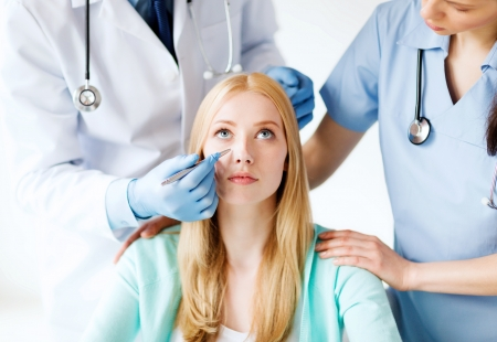 cosmetic surgery: healthcare, medical and plastic surgery concept - plastic surgeon and nurse with patient in hospital