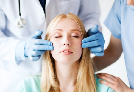 facial treatment: healthcare, medical and plastic surgery concept - plastic surgeon and nurse with patient in hospital