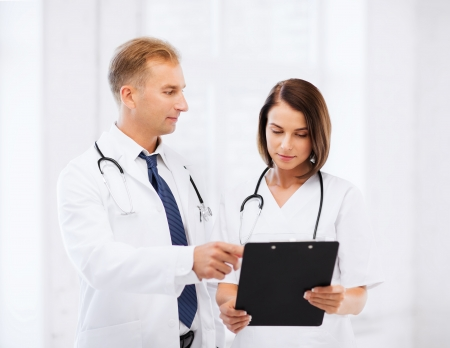 health professionals: healthcare and medical concept - two doctors discussing diagnosis Stock Photo
