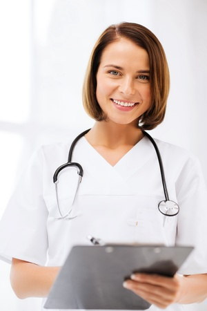 hospital staff: healthcare and medical concept - female doctor with stethoscope writing prescription