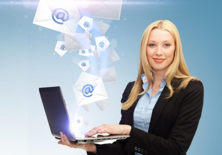 email envelope: business, communication and internet concept - businesswoman holding laptop with email sign Stock Photo
