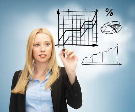 business, finances and economics - businesswoman drawing graphs in the air photo