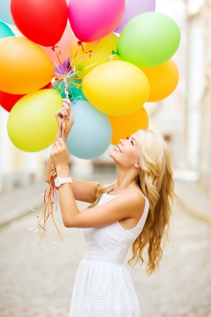 graduation party: summer holidays, celebration and lifestyle concept - beautiful woman with colorful balloons in the city