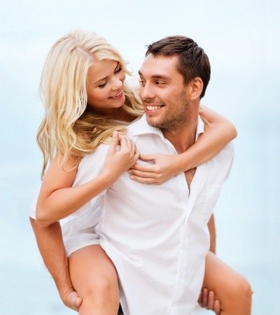 flying man: summer holidays, celebration and dating concept - couple at seaside