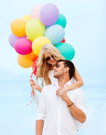 summer holidays, celebration and dating concept - couple with colorful balloons at seaside photo