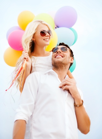 summer holidays, celebration and dating concept - couple with colorful balloons photo