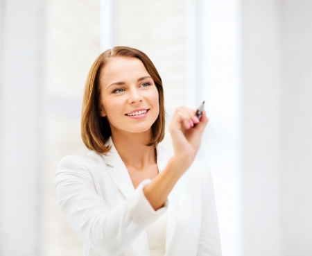 business, office, technology and education concept - smiling woman writing with pen in the air photo