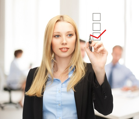 questionnaires: business and technology concept - businesswoman drawing checkmark on virtual screen