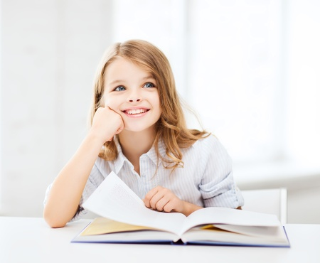 kids reading book: education and school concept - little student girl studying at school
