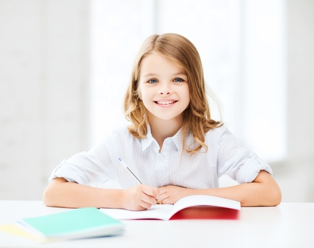 girl notebook: education and school concept - little student girl studying at school