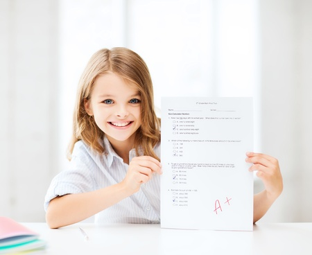 education and school concept - little school girl with test and A grade at school Stock Photo