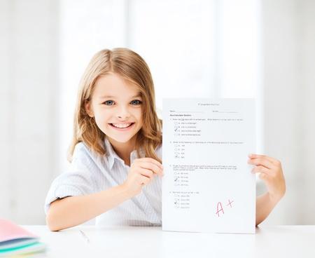 La educación y la escuela concepto - pequeña niña de la escuela con la prueba y un grado en la escuela Foto de archivo - 21575294