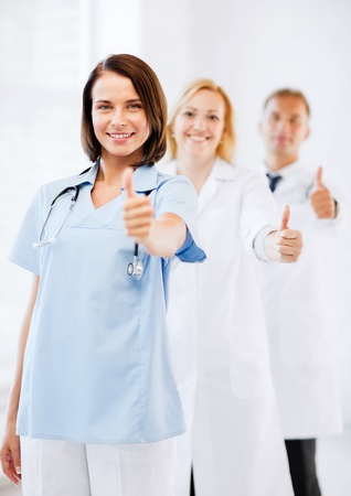 physiotherapists: healthcare and medical concept - team of doctors showing thumbs up