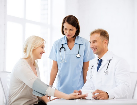 arterial: healthcare and medical concept - doctor and nurse with patient measuring blood pressure Stock Photo