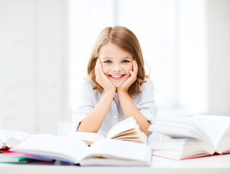 children reading books: education and school concept - little student girl studying and reading book at school