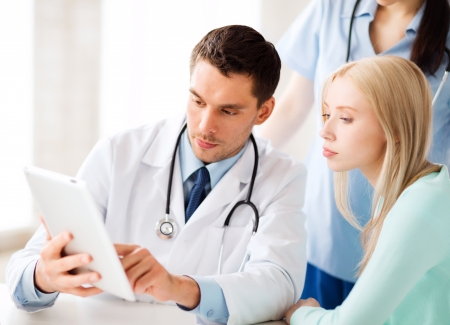 healthcare, medical and technology - doctor showing something patient on tablet pc in hospital Stock Photo