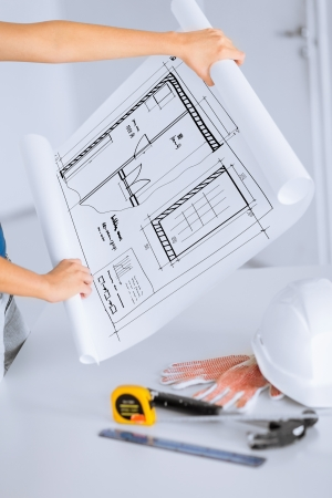 metric: architecture and home renovation concept - woman with blueprint, flexible ruller, helmet and hammer
