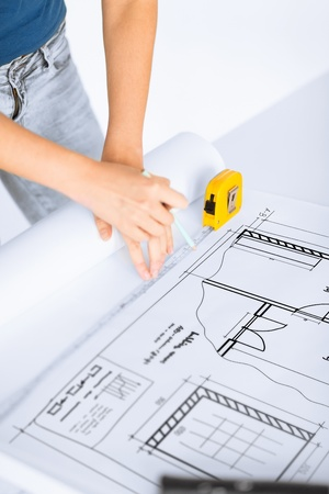 architecture and home renovation concept - architect drawing on blueprint using flexible ruler photo