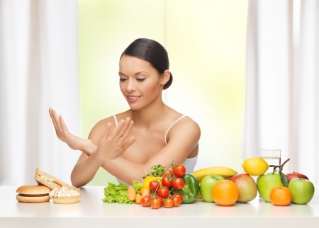 refusing: healthy and junk food concept - woman with fruits rejecting hamburger and cake