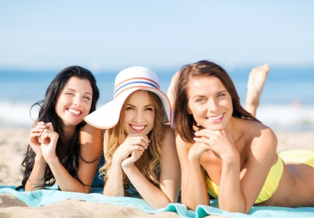sunbathe: summer holidays and vacation - girls in bikinis sunbathing on the beach