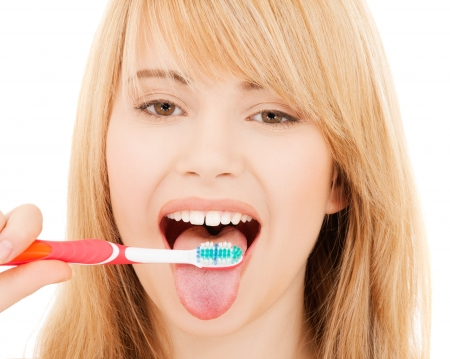 girl tongue: healthcare, medical and stomatology concept - teenage girl with toothbrush Stock Photo