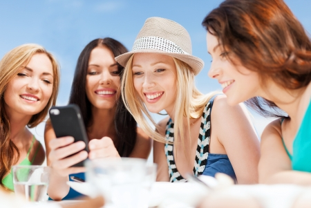 summer holidays, vacation and technology - girls looking at smartphone in cafe on the beach Stock Photo - 21680273