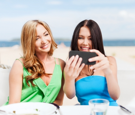 summer holidays, vacation and technology - girls taking photo with smartphone in cafe on the beach photo